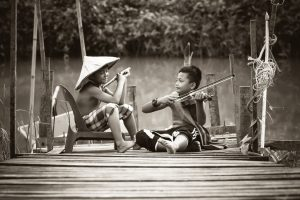 two kids setting on bridge, feeling simple with country life